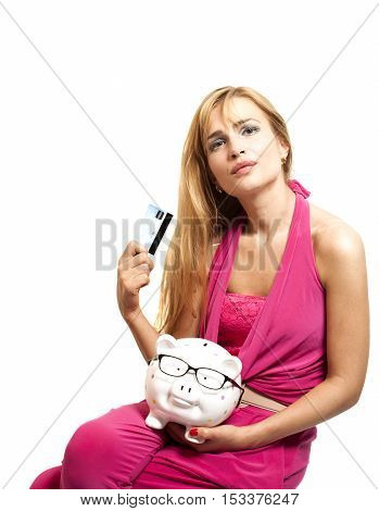 Happy young woman holding piggy bank with eyeglasses and credit card isolated on white