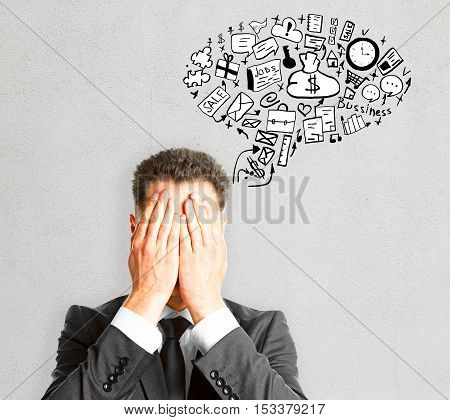 Businessman covering face with hands on concrete background with creative business sketch. Success concept
