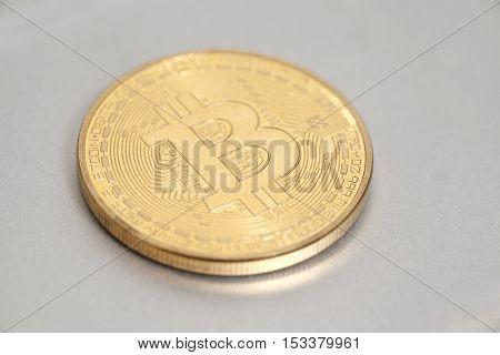 Golden Bitcoin coin on a metal surface