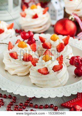 Pavlova meringue cake decorated with fresh strawberry and cape gooseberry on festive background