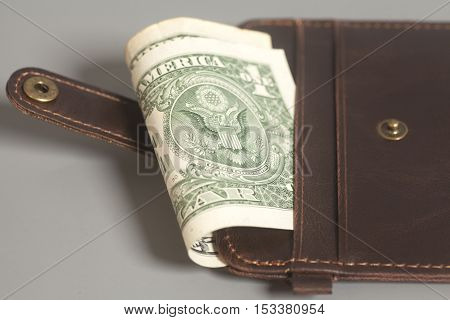 Brown Leather Wallet With One Dollars On Gray Background
