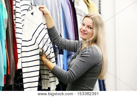 Woman in clothing shop. Girl in clothes shop
