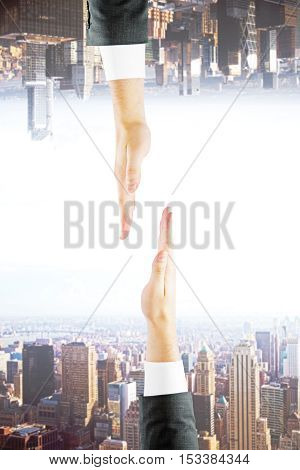 Two businessman hands on abstract upside down city background. Partnership concept