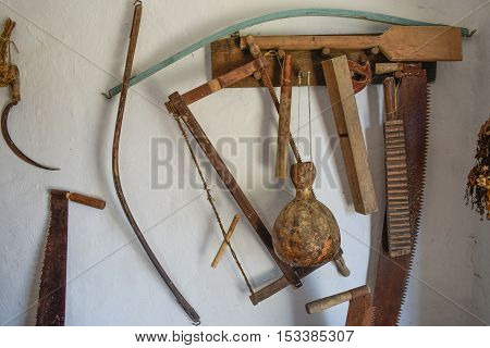 Vintage Tools On The Wall. Saws, Ax, Sickle And Other Vintage Instruments