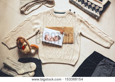 Autumn or winter children's outfit clothes. Top view fashion trendy look of baby clothes with greeting card with cutest newborn baby and accessories for the fall or winter.