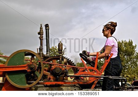 ROLLAG, MINNESOTA, Sept 1. 2016: An unidentified young lady operates a restored steam engine at the annual WCSTR farm show in Rollag held each Labor Day weekend where 1000's attend annually