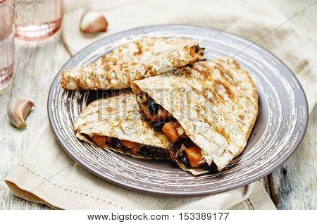 Black beans spiced sweet potato quesadilla on wood background