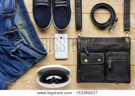 Young men's accessories in casual style, fashion industry, bag, jeans, sneakers, eyewear, belt, mobile phone on brushed wood background, clothes and shoes for spring or summer season