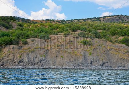 Mountain range with vegetation rises above sea level.
