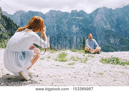 Travelers or hikers takes photos in the mountains. Mangart is a mountain in the Julian Alps located between Italy and Slovenia. Travel Freedom Lifestyle concept.