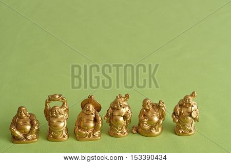 Figurines of a laughing and cheerful golden Buddhas