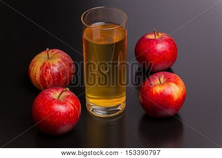 Glass of apple juice and a red apples on a dark wooden background