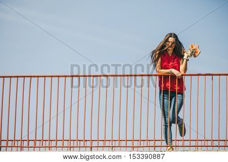 Cool skate young long haired girl holding skateboard on the urban bridge. Active lifestyle funky summertime. Outdoor trendy sport teen walk.