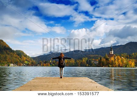 Beautiful woman standing on a wooden pier on the background with Bled Castle and Church on the Island on the Lake Bled Slovenia. Autumn time in Europe.