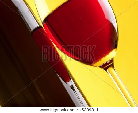 Glass and bottle of red wine on yellow background
