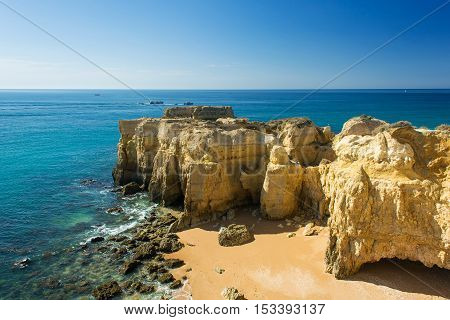 a view of beautiful sandy beach Pria do Castelo on Atlantic ocean with cliff and rock formation in Albufeira Algarve region Portugal