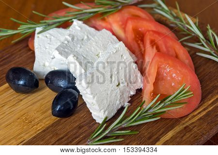 Fresh salad with tomatoes, feta cheese and olive on wooden background