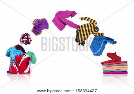 colorful clothing fly out of pile and falls into a backpack on white background