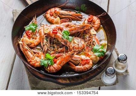 Fried prawns served on hot pan on old wooden table