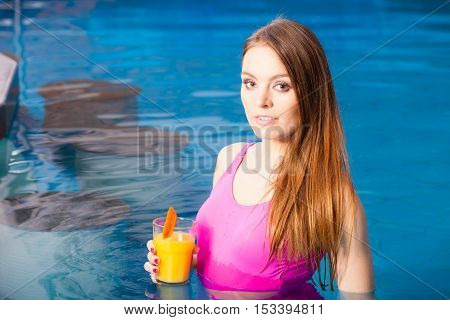 Relax spa wellness concept. Charming woman having fun with cocktail drink alcohol. Pretty girl relaxing at swimming pool enjoying the water