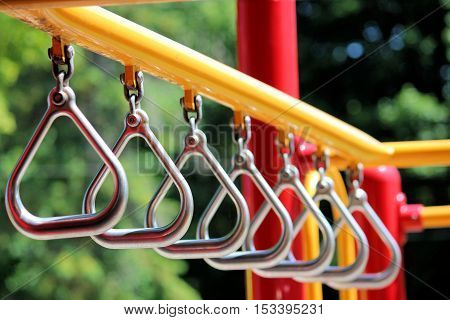 silver rings on yellow and red playground equipment