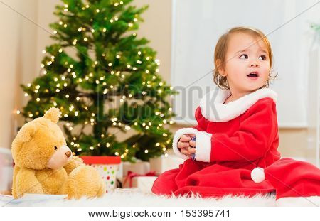 Little Girl Playing In Front Of The Christmas Tree