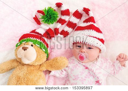 Baby Girl In A Christmas Hat With Her Teddy Bear