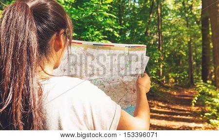 Woman in reading a map on forest trail