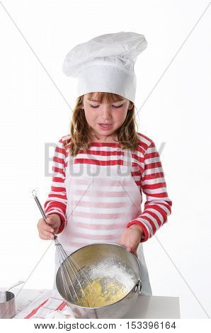 Cute Little Girl With a Chef Hat and Apron Baking.  She is using a whisk to mix eggs and other ingredients.