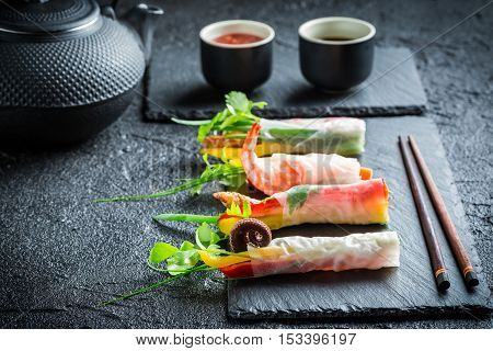 Fresh spring rolls wrapped in rice paper on black rock