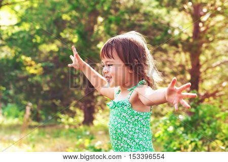 A happy smiling toddler girl playing outside