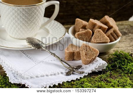 Brown cane sugar. Refined sugar. Sugar beautiful figures. A Cup of coffee. Silver spoon. White lace doily. The old boards. Vintage style.