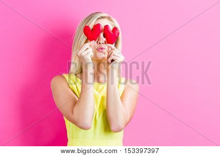 Happy Young Woman Holding Heart Cushions