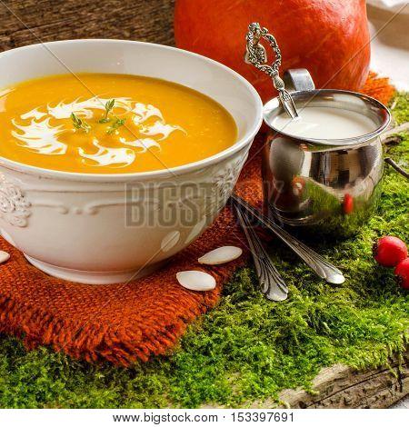 Pumpkin soup. White vintage plate. Silverware. Vintage spoon. Cream in a small pitcher. Autumn still-life. Background - old Board. Orange napkin.