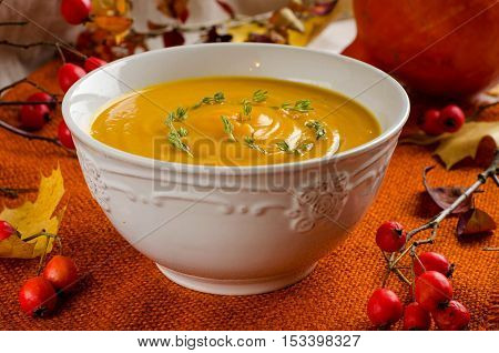 Pumpkin soup. Rustic background. Selective focus. White bowl. Orange napkin. The red berries of rose hips. Autumn yellow leaves. Autumn still-life.