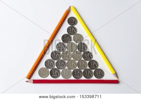 Rubles and pencils laid out in the form of a pyramid