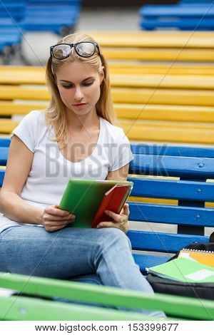 Student looks at Tablet sitting on bench on street