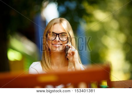 Young smiling girl talking on phone in street amid green trees