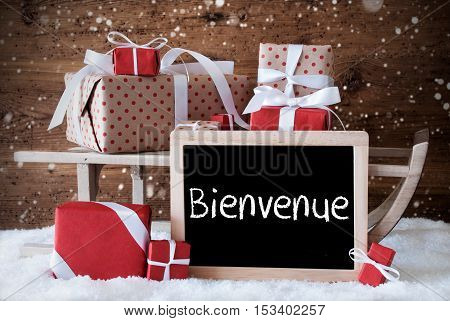 Chalkboard With French Text Bienvenue Means Welcome. Sled With Christmas And Winter Decoration And Snowflakes. Gifts And Presents On Snow With Wooden Background.
