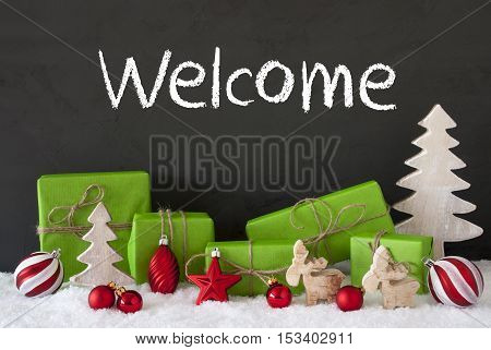 English Text Welcome. Green Gifts Or Presents With Christmas Decoration Like Tree, Moose Or Red Christmas Tree Ball. Black Cement Wall As Background With Snow.