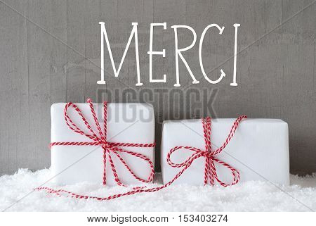 French Text Merci Means Thank You. Two White Christmas Gifts Or Presents On Snow. Cement Wall As Background. Modern And Urban Style.