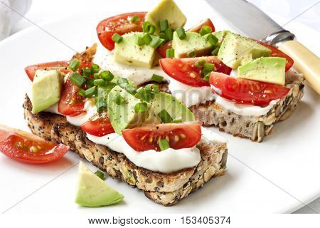 Avocado, cream cheese and tomatoes on wholewheat toast.  Topped with chives.