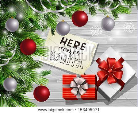 Christmas New Year design light wooden background with christmas tree and silver and red balls and greeting card with handwritten words Here comes Santa with gift boxes