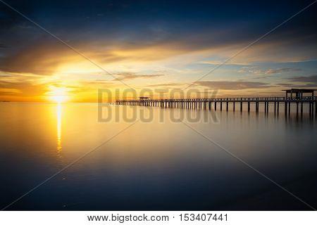 Wooden bridge into the sea at sunset