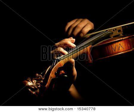 Músico tocando violín aislada en negro