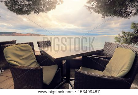 Emty table and chairs on sea background