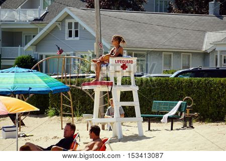 HARBOR SPRINGS, MICHIGAN / UNITED STATES - AUGUST 3, 2016: A life guard protects swimmers at the Zorn Park Public Beach near downtown Harbor Springs.