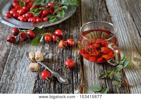 Rose hip tea in glass cup and berries on vintage plate