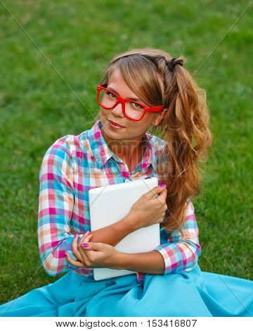 Lovely attractive girl with a laptop. She smiles and sits on a green lawn in the park. A student takes a break from lessons. Shooting with a high angle.