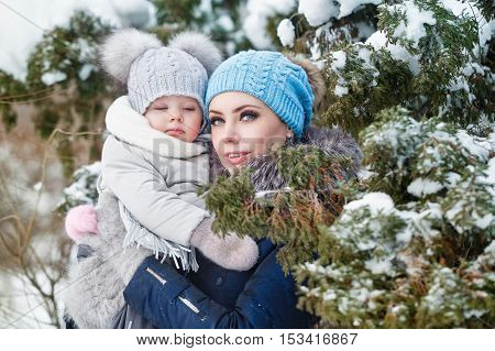 Mother and young daughter embracing in a winter park. Mother and daughter in her arms. Happy family. Childhood and parenthood happiness. Cuddle.